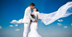 Hochzeitspaar in weiß vor einem blauen Himmel