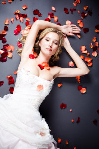Beautiful sexy bride lying on the floor among red rose petals