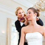 Frisör steckt einer Braut die Frisur