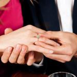Mann steckt der Verlobten Ring an den Finger