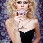 Beautiful woman with purple drink in martini glass